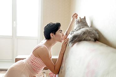 Curious Caucasian woman admiring cat on sofa