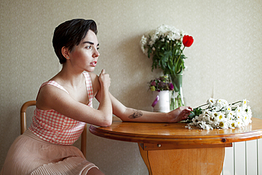 Pensive Caucasian woman sitting at table with flowers