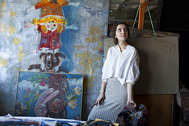 Caucasian artist holding paintbrush and palette