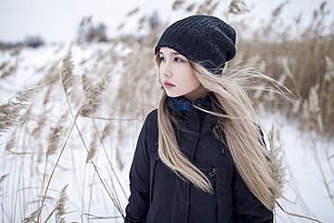 Wind blowing hair of Asian teenage girl in winter