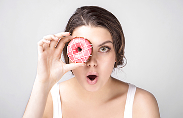 Surprised Caucasian woman holding donut over eye