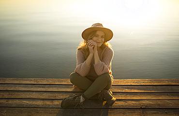 Smiling Caucasian woman sitting on dock of lake