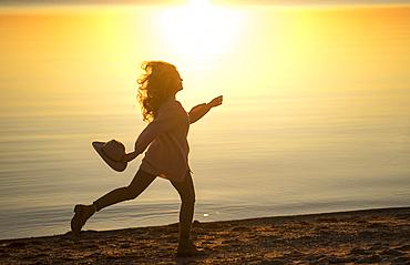Caucasian woman running on beach holding hat