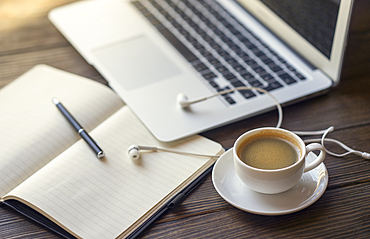 Earbuds with notebook and coffee near laptop