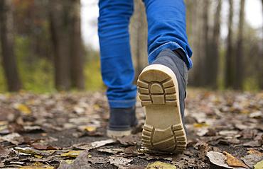 Sole of shoe of Caucasian boy walking on autumn leaves