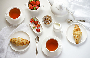 Tea with croissants and strawberries