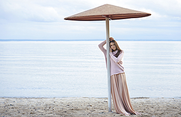 Pensive Caucasian woman leaning on beach umbrella