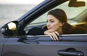 Pensive Caucasian woman leaning in car window