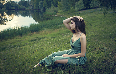Caucasian woman sitting in grass with wildflowers near lake