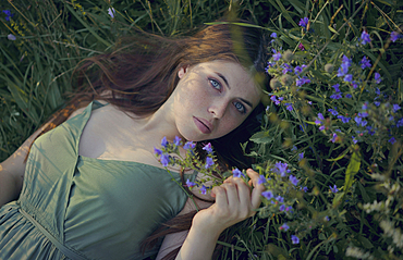 Caucasian woman laying in grass with wildflowers