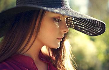 Close up of pensive Caucasian teenage girl wearing hat