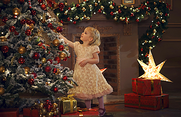 Caucasian girl decorating Christmas tree