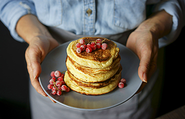 Close up of Caucasian woman holding plate of pancakes