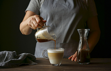 Caucasian woman pouring coffee into latte
