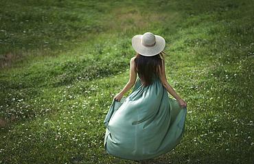 Caucasian woman wearing green dress in field