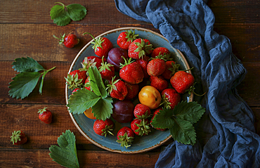 Strawberries and plums on plate