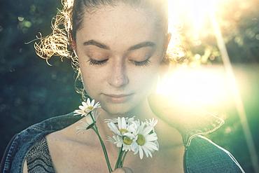 Caucasian woman smelling flowers