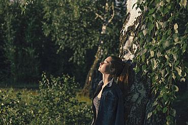 Caucasian woman leaning on tree trunk