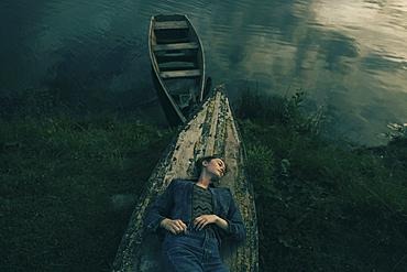 Caucasian woman laying on upside-down boat near lake