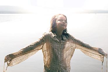 Caucasian girl wearing wet shirt near sunny lake