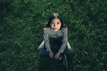 Smiling Caucasian teenage girl sitting in grass