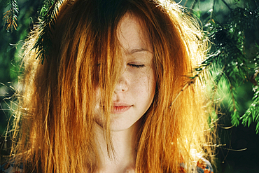 Close up of Caucasian teenage girl near pine tree