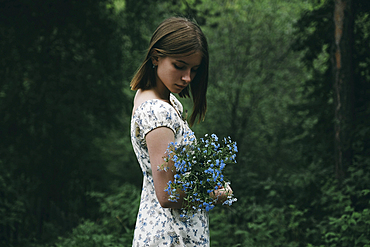 Caucasian woman holding flowers in forest