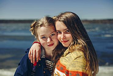 Caucasian sisters hugging on beach