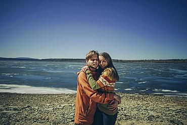 Portrait of Caucasian couple hugging on beach