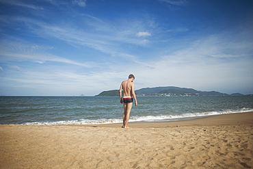 Pensive Caucasian man standing on beach