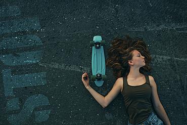 Caucasian teenage girl laying on pavement with skateboard