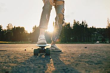 Legs of Caucasian teenage girl standing on skateboard