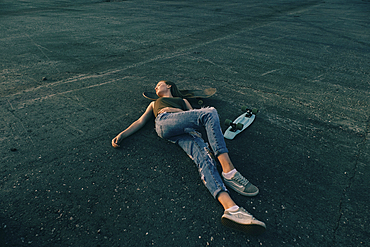 Caucasian teenage girl laying on pavement with head on skateboard