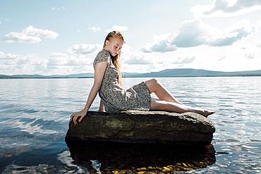 Caucasian teenage girl sitting on rock in ocean