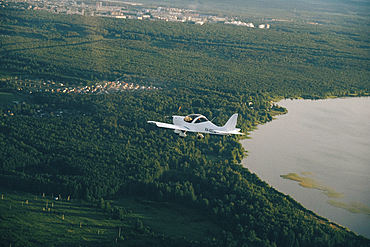 Aerial view of airplane flying over trees