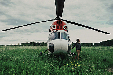 Caucasian woman standing near helicopter in field