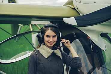 Caucasian woman wearing a headset near airplane