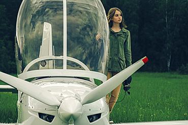 Caucasian woman standing near an airplane cockpit
