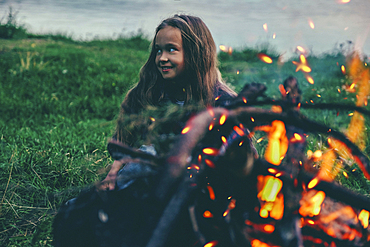 Caucasian girl sitting near campfire
