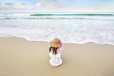 Woman sitting on beach near ocean waves