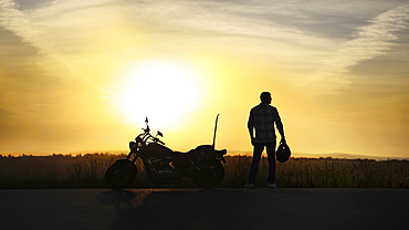Silhouette of man holding helmet near motorcycle at sunset