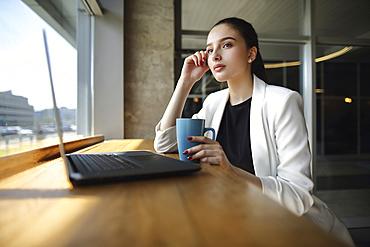 Pensive Caucasian woman drinking coffee near laptop