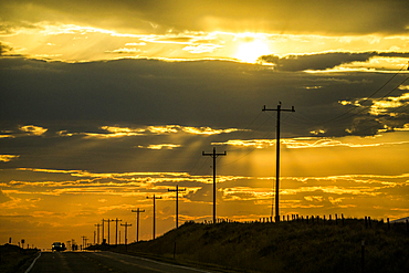 Road and utility poles at sunset