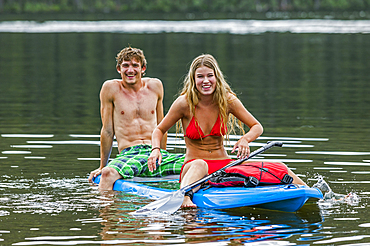 Caucasian couple straddling paddleboard