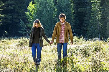 Caucasian couple walking in field holding hands