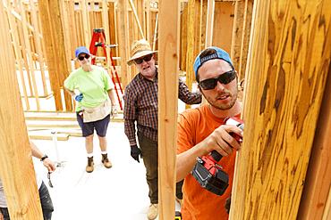 Volunteer using drill at construction site