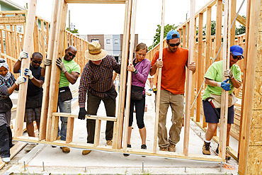 Volunteers lifting wall at construction site