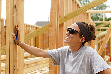 Smiling Caucasian woman leaning on frame a construction site