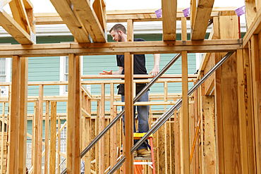 Caucasian man standing on ladder at construction site