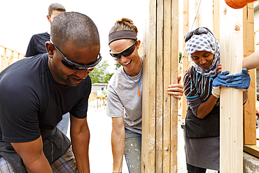 Volunteers holding lumber at construction site